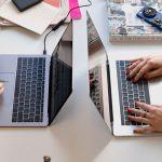 laptops side by side on a shared office desk